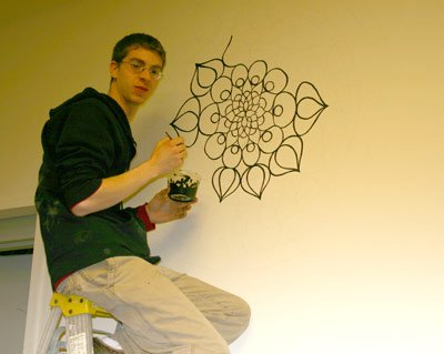 Vinnie Tocco paints the wall at the Atrium
