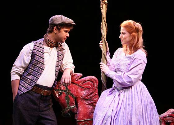 Billy Bigelow (John Grieco) and Julie Jordan (Alison Drew) meet aboard the carousel where he is the barker.
