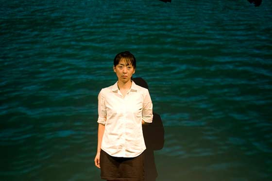 Haerry Kim in front of the projected image of the sea the abducted women cross from Korea to Japan.