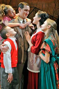 George Bailey (Brad Heikes) surrounded by his adoring family (L to R) Tommy (Aidan Fecko), Zuzu (Belle Babcock), wife Mary (Caroline Galvez), and Beth (Chezmin Sheehan). (Photo: Theresa M. Thibodeau)