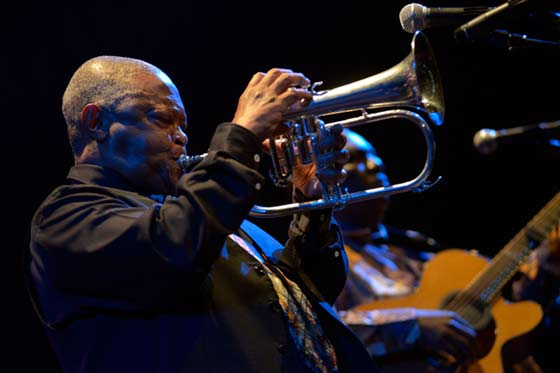 Hugh Masekela blowing the flugelhorn while Vusi Mahla  strums the guitar