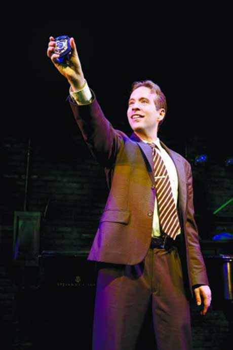 "Ian Lowe has a solo song, ""Protocol Says"" in his role as a detective in Murder for Two. Photo by Joan Marcus."