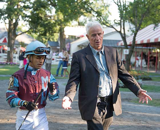 Trainer Nick Zito giving riding instructions to jockey Eric Cancel in the paddock.