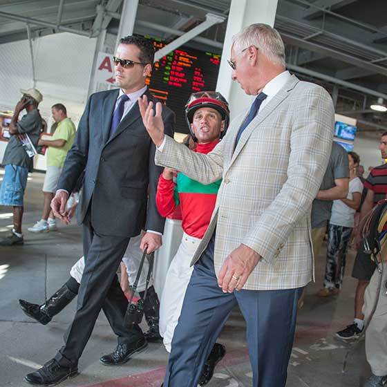 Pletcher leaving the track via the 'jockey lane' in the Clubhouse, discussing the race just finished with jockey Javier Castellano.