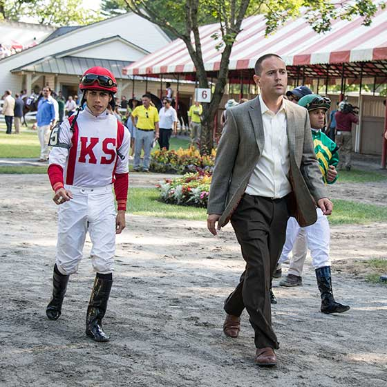 Trainer Chad Brown heading to 'Riders Up' in the paddock with jockeys Ortiz and Castellano who are riding his two entries in the race.