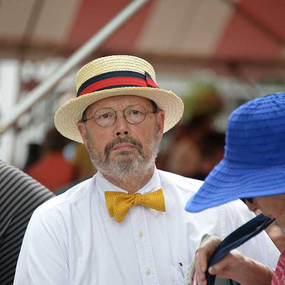A dapper racing fan watches horses going from the paddock to the track for a race near the Paddock Bar.