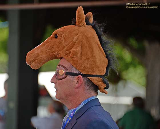 A two headed racing fan horses around on opening day.