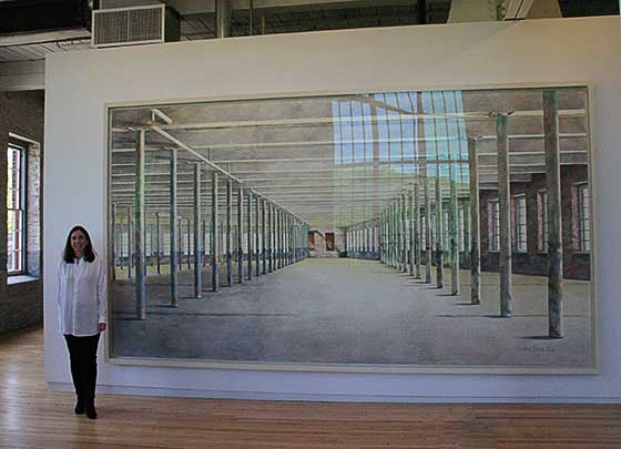 Barbara Prey stands next to her massive watercolor painting of the interior of Building 6.
