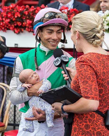 Jose Ortiz holds his 4 week old child, Leilani, in the winners circle after winning Grade II The Honorable Miss on Paulassilverlining. 7/29/2017